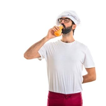 Szef kuchni pije sok pomarańczowy
