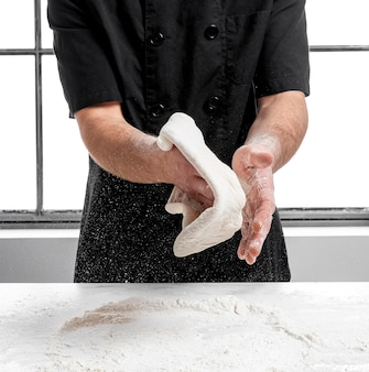 Szef kuchni pizzy robi ciasto na pizzę
