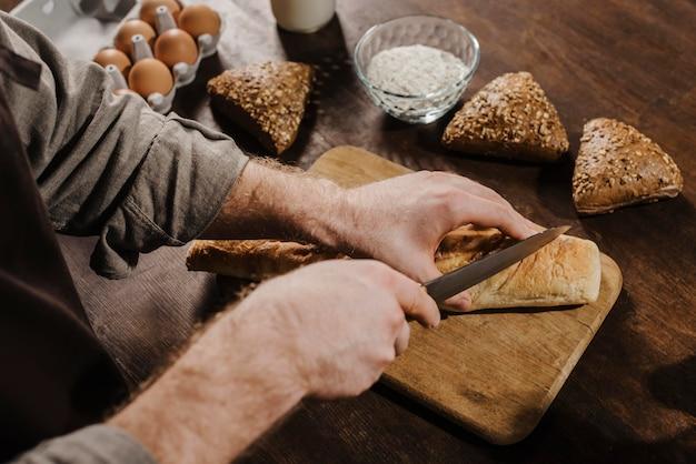 Szef kuchni pod wysokim kątem cięcia chleba