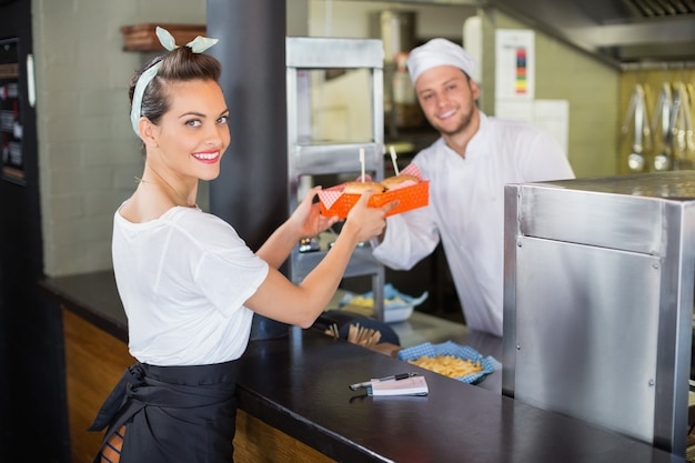 Szef kuchni podaje burgery kelnerce w kuchni