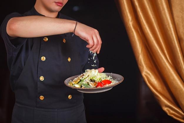 Szef kuchni podaje sałatkę cezar z parmezanem.