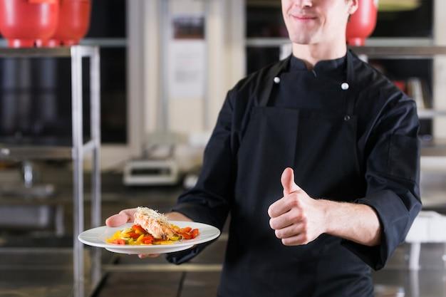 Szef kuchni pokazuje jego naczynie