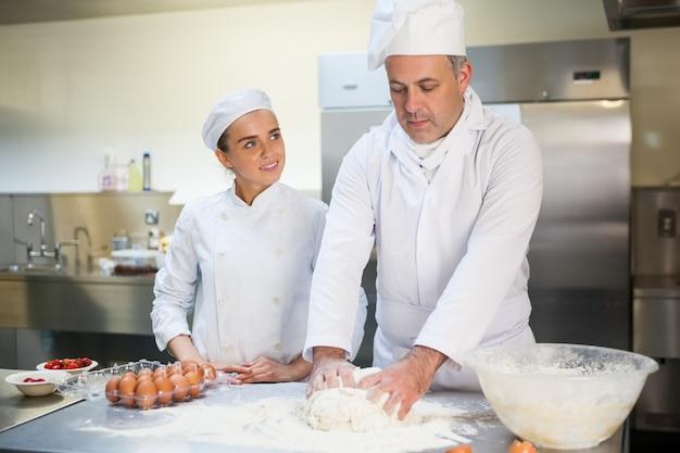 Szef kuchni pokazuje szczęśliwy praktykant, jak przygotować ciasto