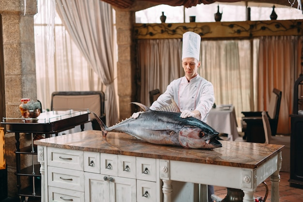 Szef kuchni pokroił dużą rybę z tuńczyka w restauracji.