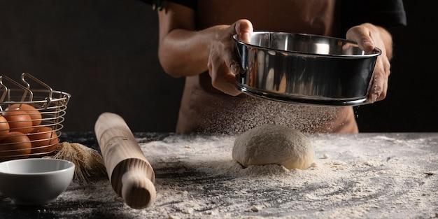Szef kuchni pokrywający ciasto mąką