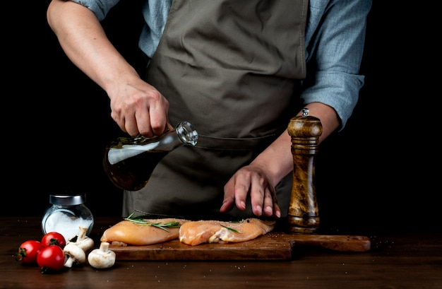 Szef kuchni polewający pierś kurczaka sosem