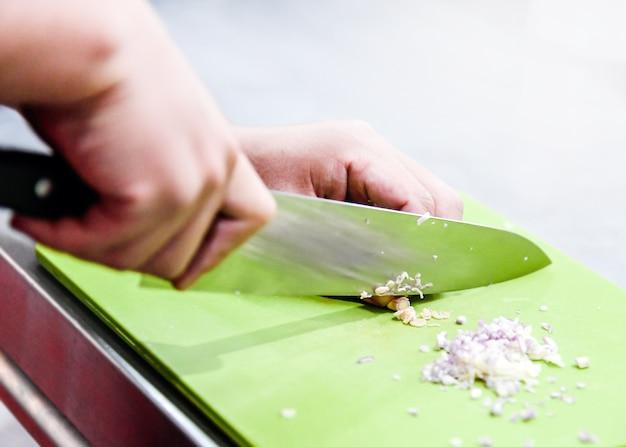 Szef kuchni posiekany trawę cytrynową. szef kuchni przygotowuje potrawy w kuchni