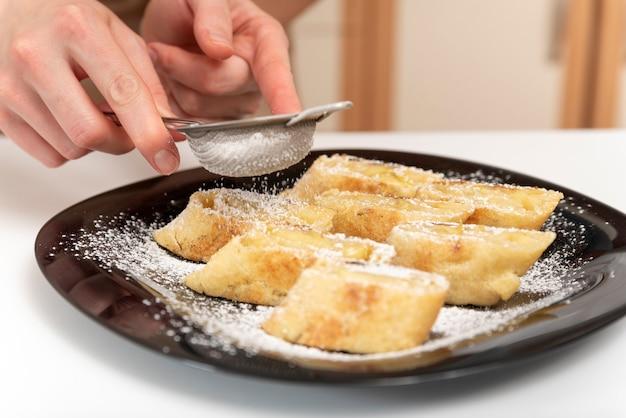 Szef kuchni posypuje bułkę z jabłek cukrem pudrem. pasza strudla.