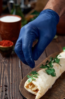 Szef kuchni posypuje kebab kolendrą