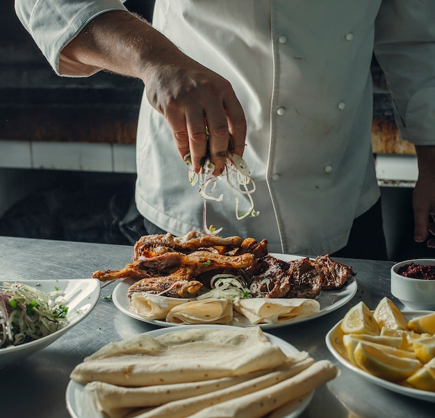 Szef kuchni posypuje krążki cebuli na talerzu kebab z kurczakiem, jagnięciną, płaskimi chlebami