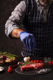 Szef kuchni posypuje solą gotowy do grillowania antrykot wołowy