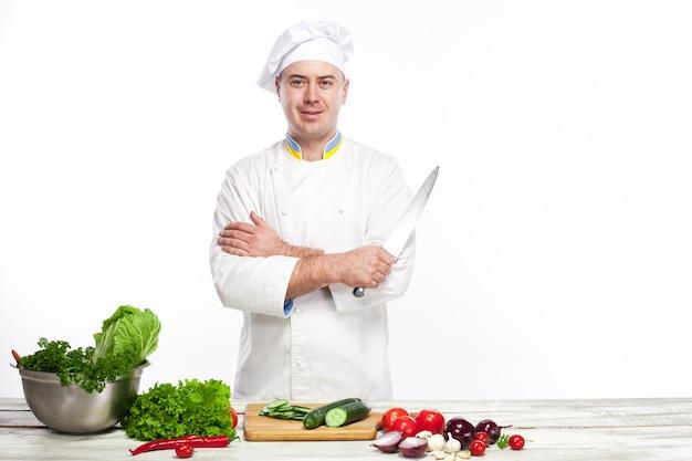 Szef kuchni pozuje z nożem w jego kuchni