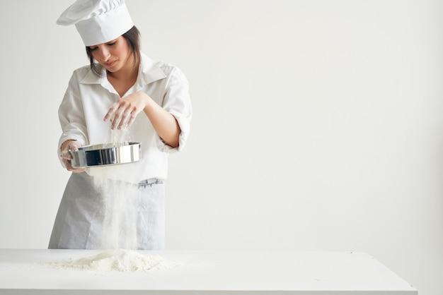Szef kuchni pracujący przy wyrobie ciasta mącznego profesjonalnie obsługuje kuchnię. zdjęcie wysokiej jakości