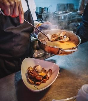 Szef kuchni prezentujący porcję małży w wykwintnym sosie