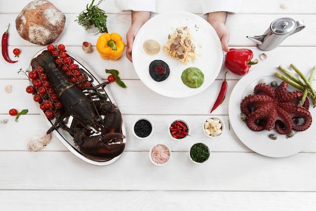 Szef kuchni prezentujący tradycyjny włoski posiłek złożony z makaronu i ravioli