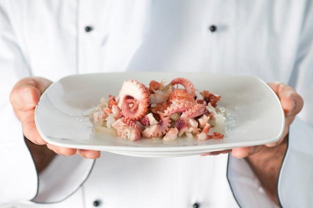 Szef kuchni prezentuje i podaje swoje danie z owoców morza