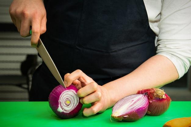 Szef kuchni próbuje pokroić czerwoną cebulę