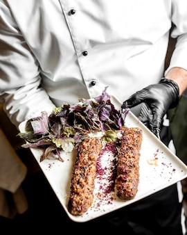 Szef kuchni przedstawia lula kebab podany z bazylią