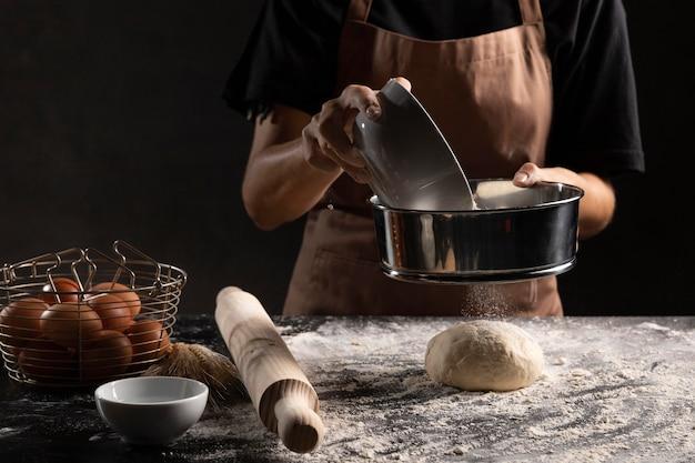 Szef kuchni przesiewa mąkę na kawałku ciasta