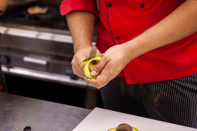 Szef kuchni przygotowuje awokado na pyszną sałatkę w kuchni restauracji