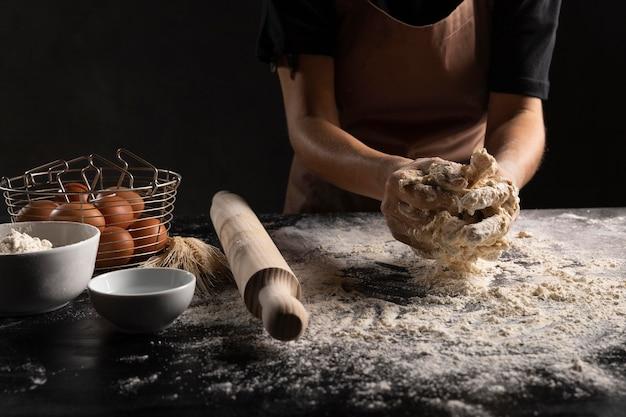 Szef kuchni przygotowuje ciasto chlebowe na stole