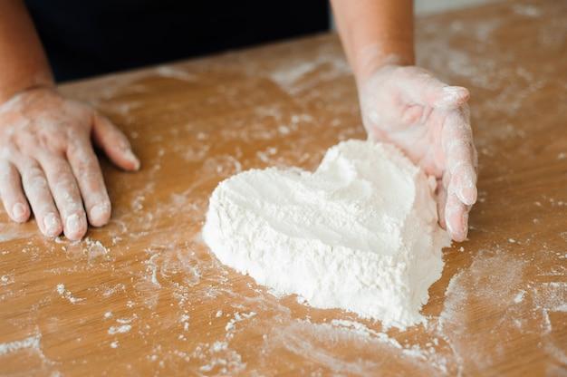 Szef kuchni przygotowuje ciasto - proces gotowania, serce mąki.