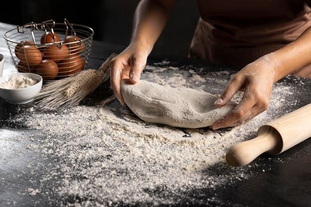 Szef kuchni przygotowuje ciasto z wałkiem i mąką