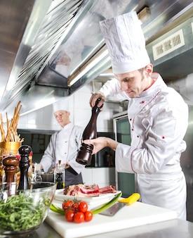 Szef kuchni przygotowuje danie w kuchni restauracji.