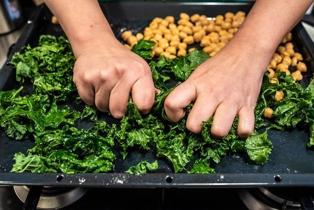 Szef kuchni przygotowuje danie z jarmużu i ciecierzycy.