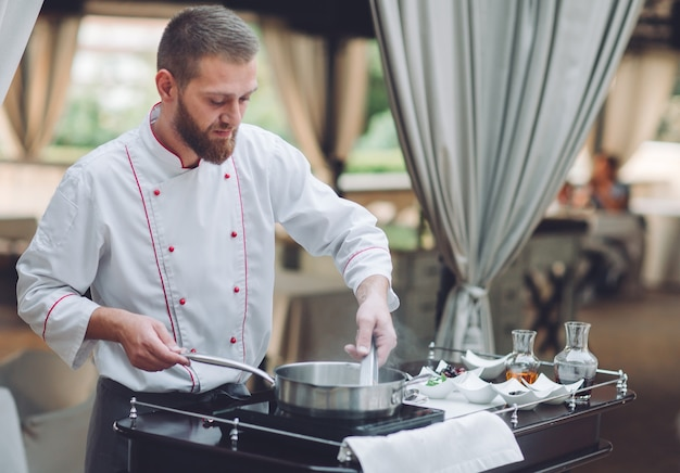 Szef kuchni przygotowuje foie gras przed gośćmi.