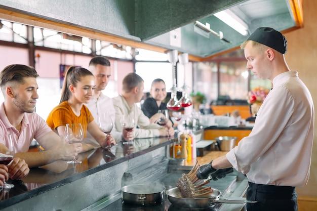 Szef kuchni przygotowuje jedzenie przed gośćmi w restauracji