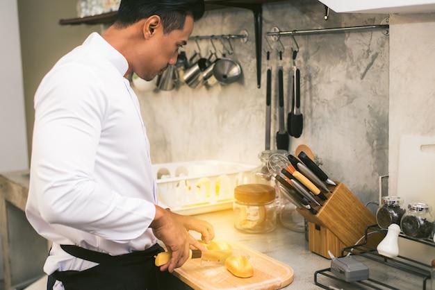 Szef kuchni przygotowuje jedzenie w kuchni w restauracji