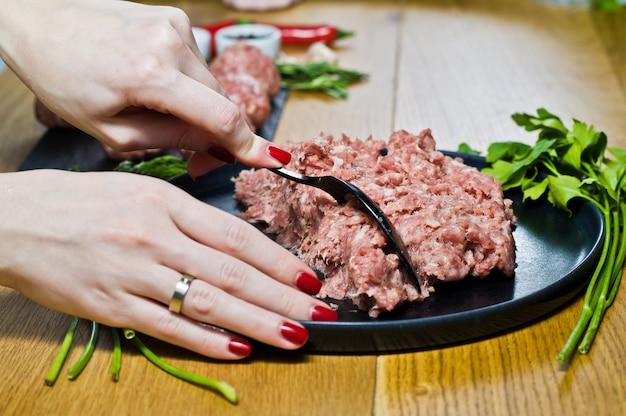 Szef kuchni przygotowuje klopsiki z surowego mięsa mielonego.