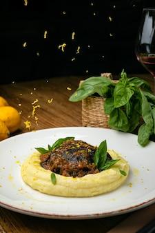 Szef kuchni przygotowuje policzki cielęce, zioła i skórkę z cytryny na talerzu. na drewnianym stole