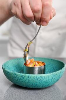 Szef kuchni przygotowuje pyszny tatar warzywny, a jego przygotowanie kończy klasą. koncepcja: szef kuchni, kuchnia, restauracja, jedzenie.