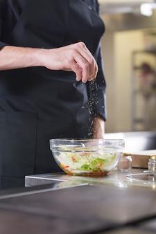 Szef kuchni przygotowuje sałatkę