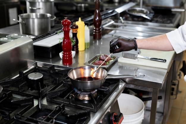 Szef kuchni przygotowuje sos na patelni z czerwonym winem