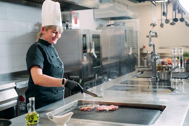 Szef kuchni przygotowuje stek w kuchni restauracji