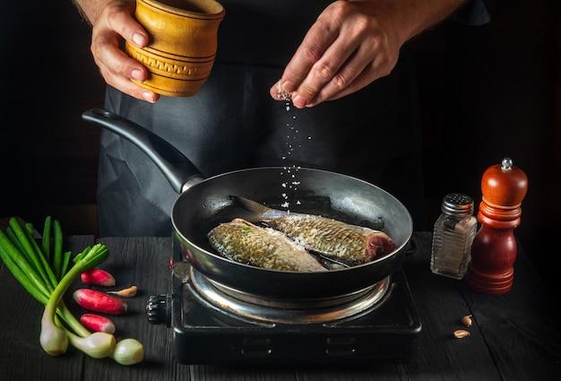 Szef kuchni przygotowuje świeżą rybę na patelni posypując solą z dodatkami. przygotowanie do gotowania ryb. środowisko pracy w kuchni restauracji.