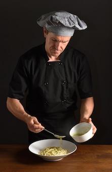 Szef kuchni przygotowuje talerz spaghetti
