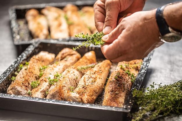 Szef kuchni przygotowuje w naczyniu do pieczenia filety wieprzowe i używa ziół.