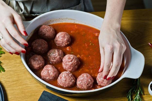 Szef kuchni przygotowuje włoskie klopsiki z surowego mięsa mielonego, umieszcza w naczyniu do pieczenia z sosem pomidorowym.