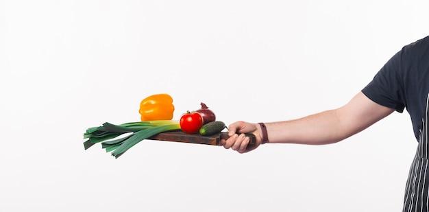 Szef kuchni ręka trzyma deskę do krojenia z warzywami