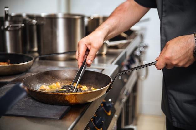 Szef kuchni restauracji gotuje czarne spaghetti na patelni ze szczypcami