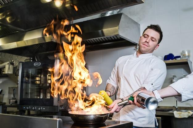Szef kuchni robi flambe w kuchni restauracji