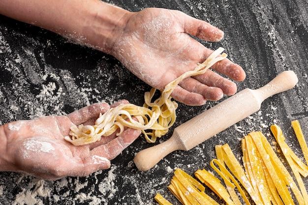 Szef kuchni robi makaronowi w pobliżu wałka do ciasta
