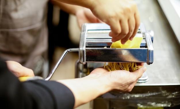 Szef kuchni robi makaronowi z maszyną, domowy robić świeży makaron