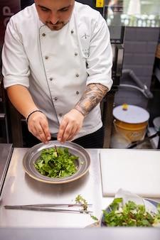 Szef kuchni robi pyszną sałatkę w kuchni restauracji
