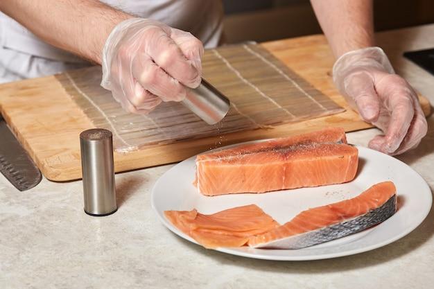 Szef kuchni robi ryby. pieprzowy stek z łososia