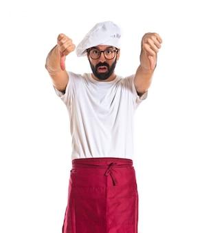 Szef kuchni robi zły sygnał na białym tle